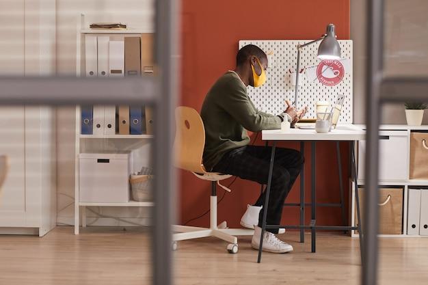 Vista laterale a figura intera al giovane afro-americano che indossa la maschera mentre si lavora alla scrivania in ufficio moderno, copia dello spazio