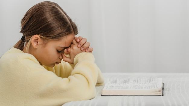Vista laterale della ragazza che prega a casa con la bibbia e lo spazio della copia