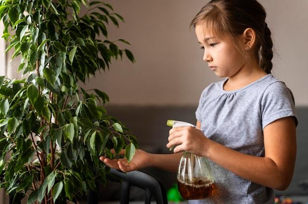 Vista laterale della ragazza che spruzza pianta con acqua