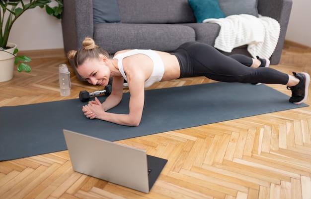 Vista laterale dell'atleta femminile sottile felice che sorride e che fa esercizio della plancia sulla stuoia vicino al computer portatile durante l'allenamento di forma fisica in linea a casa