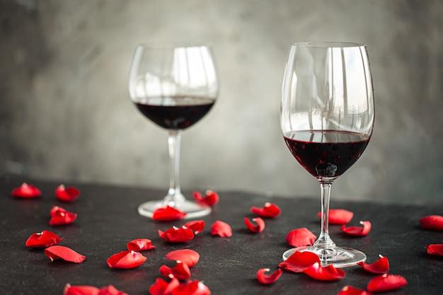 Vista laterale su un bicchiere di vino rosso con petali