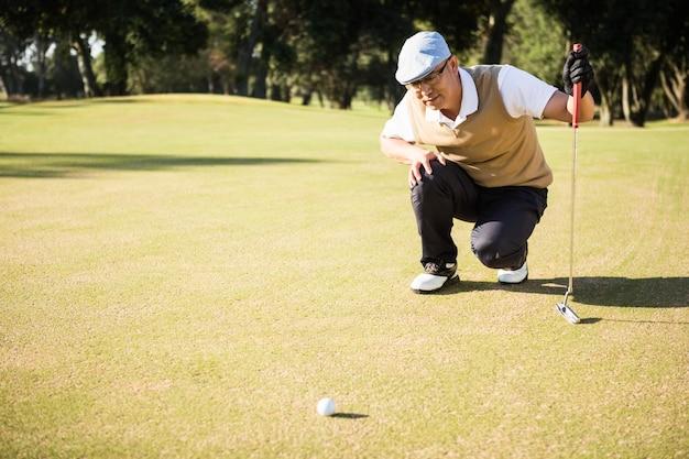 Vista laterale del giocatore di golf che si accovaccia e che guarda la sua palla
