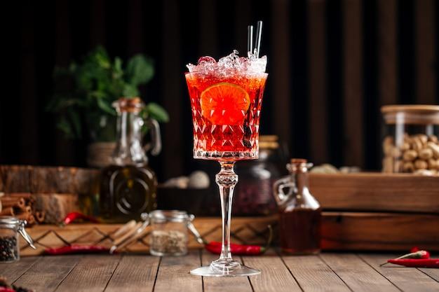 Vista laterale sul cocktail rosso gourmet in un bicchiere sullo sfondo di legno