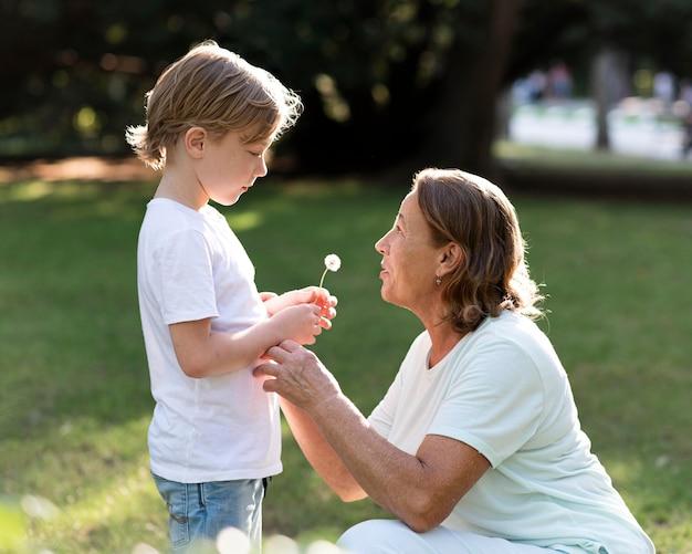 Vista laterale nonna e bambino con fiore