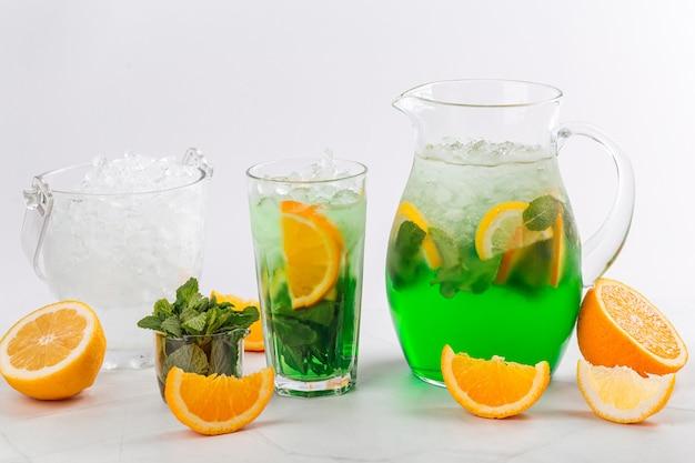 Vista laterale sulla limonata verde in una brocca e un bicchiere su fondo bianco