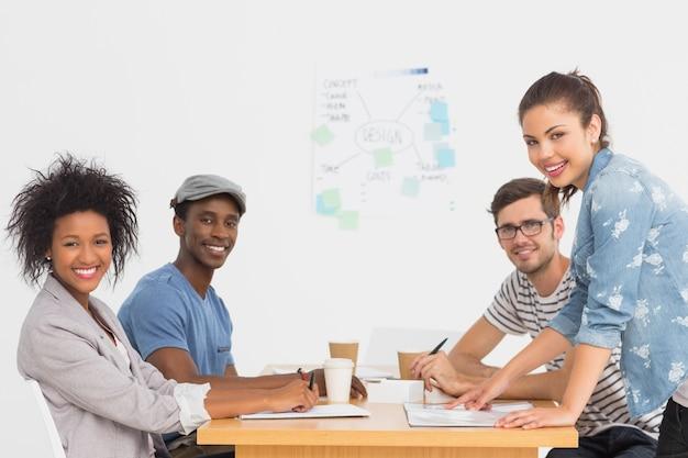 Vista laterale di un gruppo di artisti in discussione alla scrivania