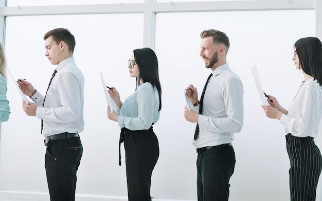 Vista laterale gruppo di dipendenti in piedi nella hall dell'ufficio. concetto di affari