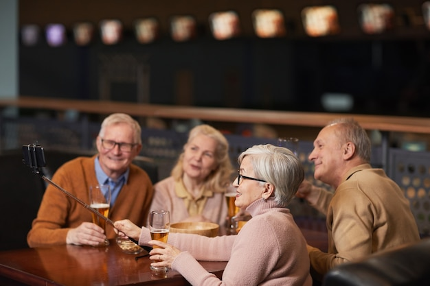 Vista laterale di un gruppo di anziani moderni che scattano foto selfie mentre bevono birra al bar e si godono la serata con gli amici, copia spazio