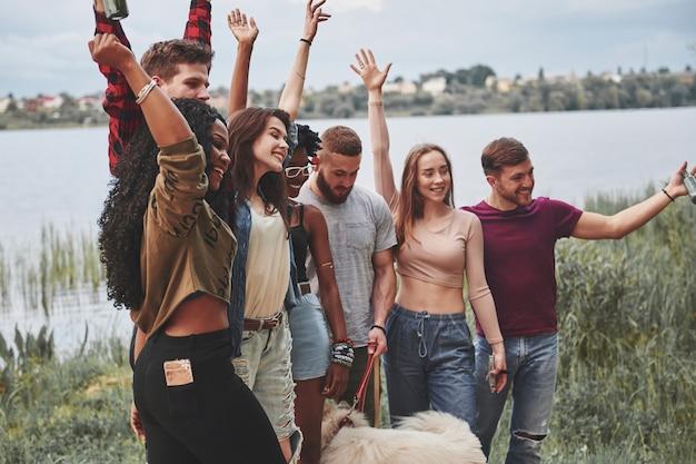 Vista laterale. un gruppo di persone fa un picnic sulla spiaggia. gli amici si divertono durante il fine settimana.