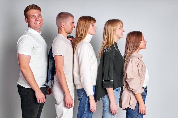 Vista laterale su un gruppo di giovani in fila in ordine decrescente