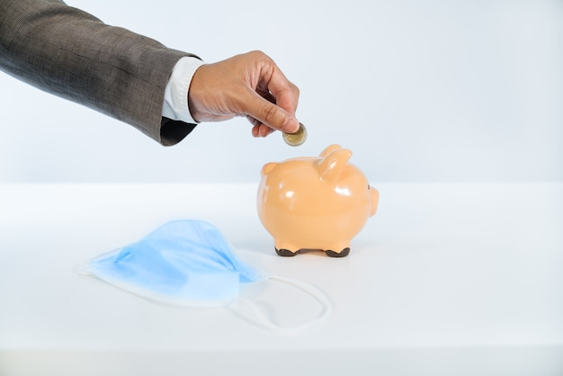 Vista laterale di una mano che inserisce una moneta in un salvadanaio in ceramica con uno sfondo bianco e una luce molto buona e una maschera per il viso a causa della pandemia di coronavirus covid19