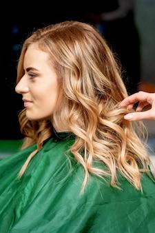 Vista laterale delle mani del parrucchiere femminile per lo styling dei capelli di una donna bionda in un parrucchiere