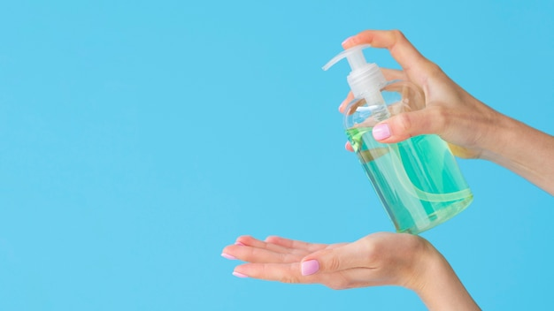 Vista laterale delle mani usando sapone liquido con spazio di copia