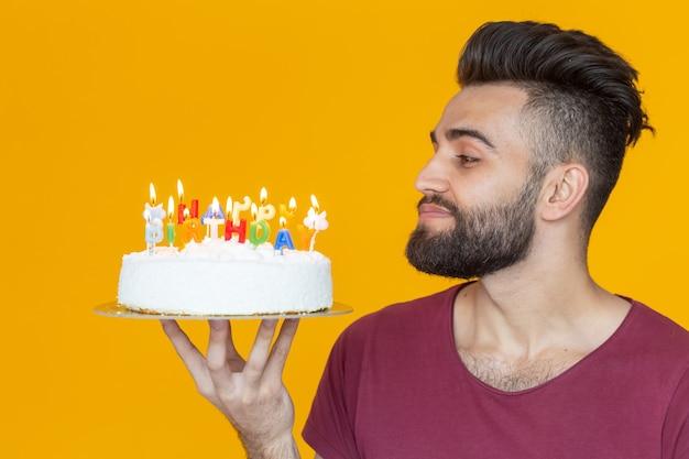 Vista laterale di un bel giovane barbuto arabo che spegne le candeline con una torta di congratulazioni in posa