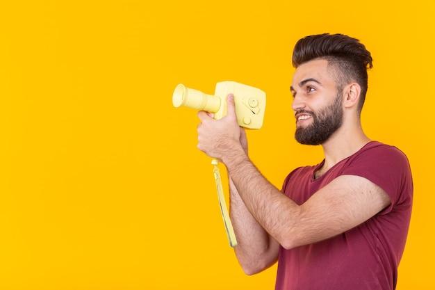 Vista laterale di un bel giovane maschio hipster con la barba spara oggetti su una videocamera vintage