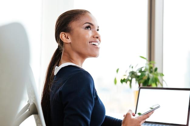 Vista laterale della donna d'affari africana felice in abito seduta al tavolo vicino alla finestra in ufficio, tenendo il telefono e guardando in alto