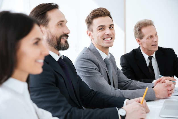 Vista laterale di happy business persone sedute al tavolo in ufficio e un uomo che guarda la telecamera