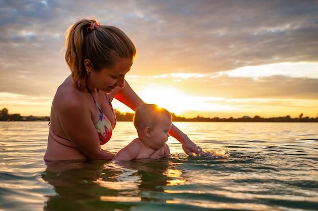 Vista laterale della madre caucasica felice che insegna a nuotare piccolo bambino sorridente adorabile in acqua di mare