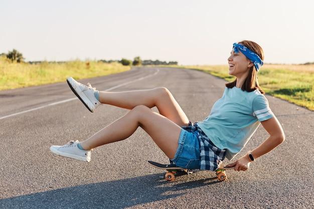 Vista laterale della donna emotiva felice seduta su skateboard per strada con le gambe sollevate, donna felicissima che indossa abiti casual divertendosi all'aperto, stile di vita positivo.