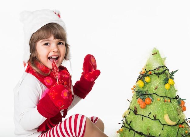 Vista laterale della bambina felice che si siede accanto all'albero di natale e che tiene il lecca-lecca.