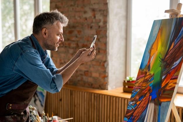 Vista laterale di felice artista di mezza età con lo smartphone che cattura foto di opere d'arte astratte su cavalletto nel suo studio