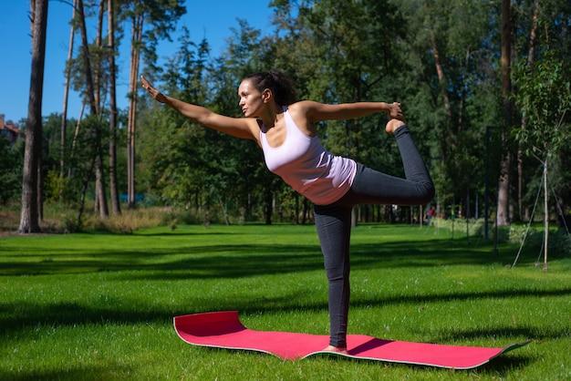 Vista laterale di una donna sorridente felice in piedi in posizione yoga su un prato verde nel parco