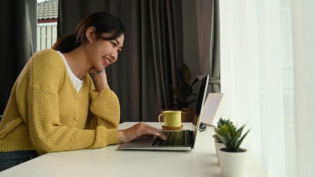 Vista laterale di felice giovane donna che guarda sullo schermo del computer portatile mentre era seduto a casa in ufficio
