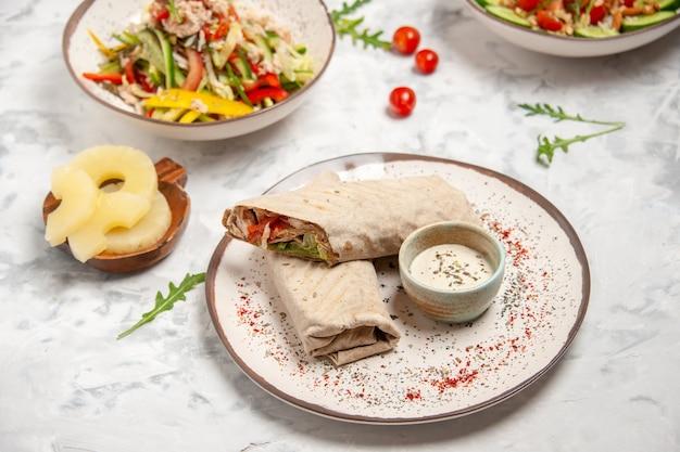 Vista laterale di insalate vegane sane ananas essiccato e impacchi di lavash sulla superficie bianca macchiata
