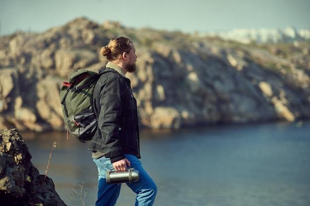 Vista laterale di un escursionista con zaino ammirando il paesaggio su alte vette e tenendo in mano un thermos. viaggi, avventura, natura, concetto di libertà.
