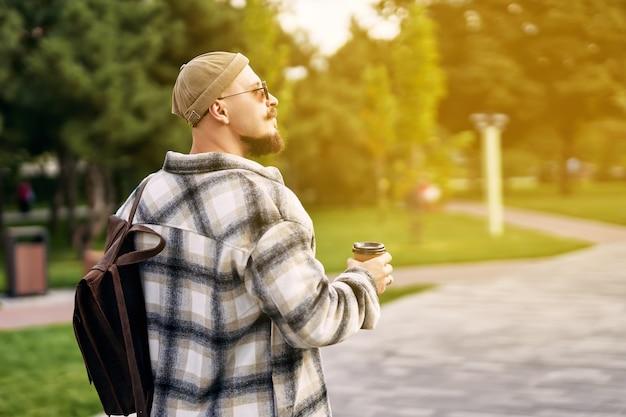 La vista laterale dello studente barbuto hipster guarda di traverso mentre cammina nel giorno di riposo del parco cittadino urbano