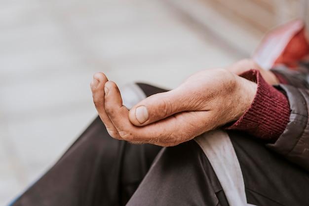Vista laterale del senzatetto tenendo la mano per chiedere aiuto