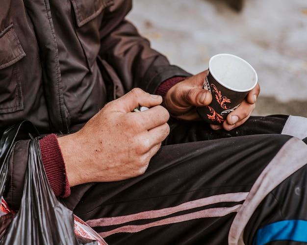 Vista laterale di un senzatetto con tazza vuota