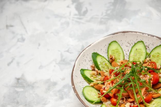 Vista laterale di insalata vegana deliziosa sana fatta in casa decorata con cetrioli tritati in una ciotola sulla superficie bianca macchiata