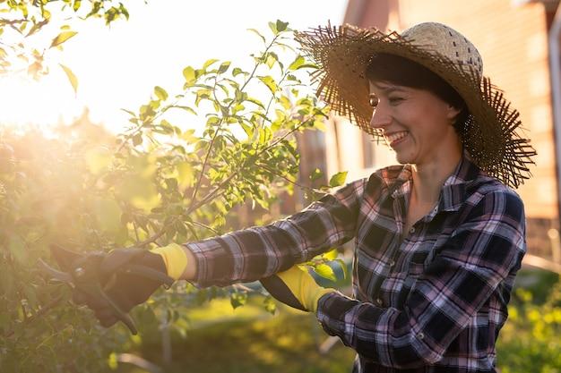 Vista laterale del giardiniere gioioso giovane donna caucasica taglia rami e foglie non necessari da un albero