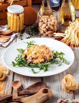 Vista laterale su julienne sotto il formaggio con rucola sul tavolo di legno