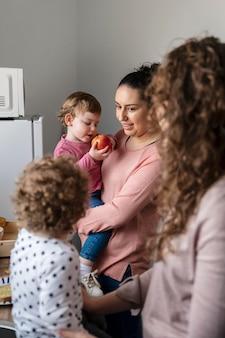 Vista laterale della famiglia lgbt a casa con i bambini