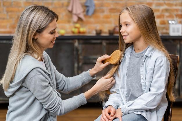Vista laterale della bambina che ottiene i suoi capelli spazzolati dal parrucchiere