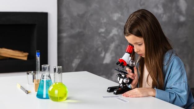 Vista laterale della bambina che osserva tramite il microscopio