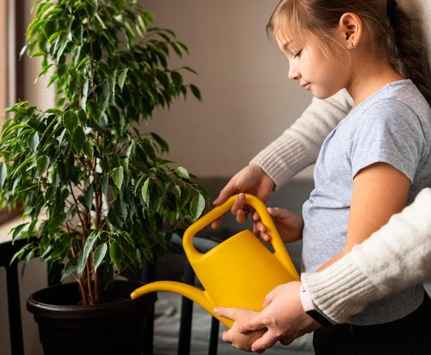 Vista laterale della bambina innaffiare la pianta a casa