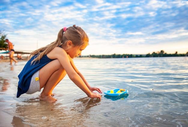 Vista laterale della piccola adorabile ragazza caucasica che gioca con minuscole anatre di gomma gialla in una piccola piscina blu, in piedi sulla sabbia della spiaggia. ragazzo attraente che si diverte, si gode le vacanze al mare, in estate.