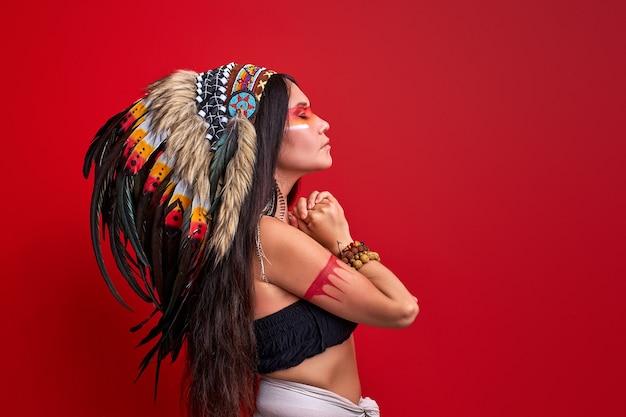 Vista laterale sulla donna sciamano dai capelli lunghi con piume sulla testa