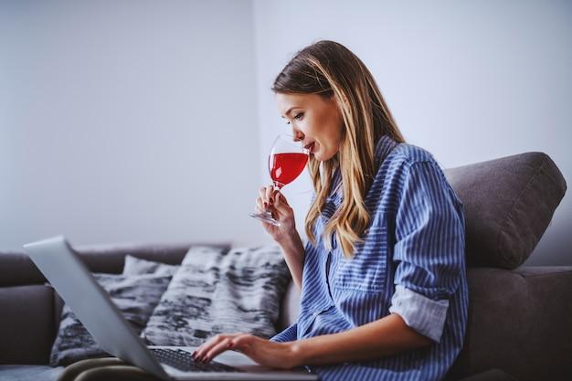 Vista laterale della bella bruna indoeuropea in camicia spogliata seduto sul divano in salotto, bere vino e utilizzando il computer portatile.