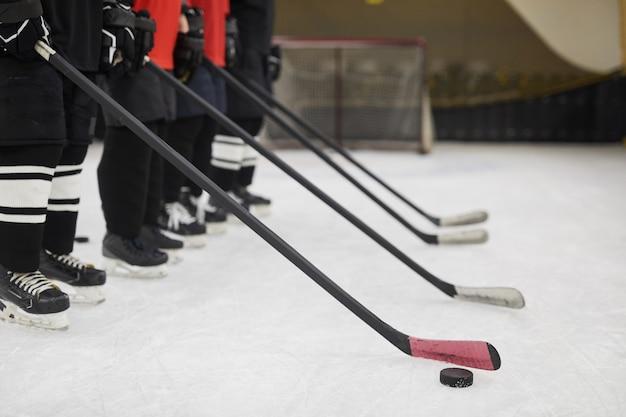 Vista laterale sezione bassa della squadra di hockey in piedi in fila pronta per la partita sul ghiaccio