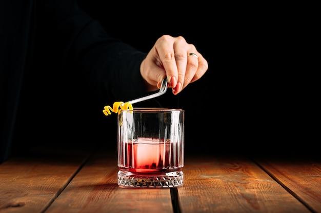 Vista laterale sulla produzione di cocktail negroni in vecchio stile di vetro sul tavolo di legno