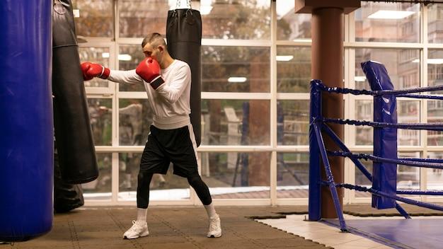 Vista laterale del pugile maschio che pratica con il sacco da boxe sul ring