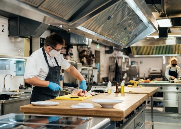 Vista laterale del cuoco unico maschio che cucina con mascherina medica in cucina