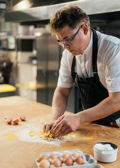 Vista laterale del cuoco unico maschio che fa pasta