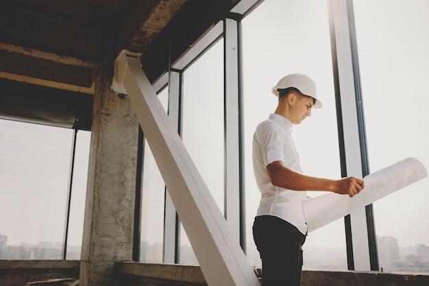 Vista laterale dell'ingegnere maschio che sta cercando nel progetto di costruzione vicino a una finestra che ispeziona come sta andando il lavoro.