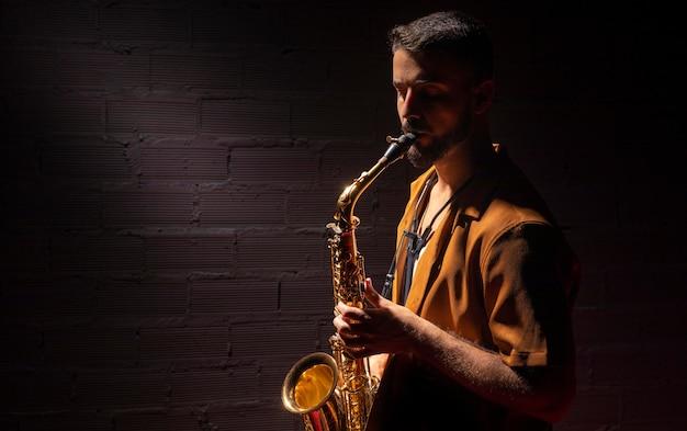 Vista laterale del musicista maschio che suona appassionatamente il sassofono
