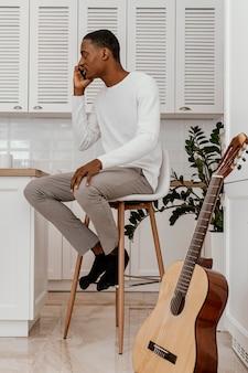 Vista laterale del musicista maschio che parla al telefono accanto alla chitarra